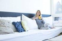 Расслабленная женщина сидит на диване с чашкой кофе — стоковое фото