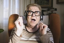 Portrait of happy elderly lady hearing music with headphones — Stock Photo