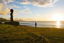 Остров Пасхи, Ханга-Роа, каменная статуэтка путешественника и Моая в комплексе Тахай Церемониал на закате — стоковое фото