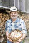 Улыбаясь хуторянин на органические фермы, холдинг корзина с яйцами — стоковое фото