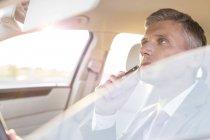 Businessman shaving in car — Stock Photo