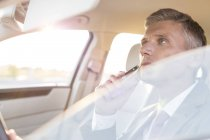 Businessman shaving in car — Stock Photo