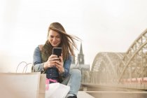 Woman with shopping bags taking a selfie — Stock Photo