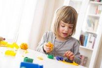 Petite fille jouer avec jaune pâte à modeler — Photo de stock