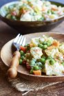 Potato salad with potatoes, carrots, peas, onions, pickles and dill on plate with fork — Stock Photo