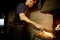 Blacksmith at work at the fireplace with metal — Stock Photo