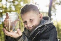 Germania, ritratto di un ragazzino sorridente che tiene il vetro con il fungo — Foto stock