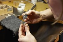 Goldsmith in workshop working on heart-shaped piece of jewelry — Stock Photo
