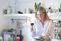 Woman in kitchen drinking wine — Stock Photo
