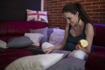 Femme enceinte utilisant un ordinateur portable à la maison, manger des fruits — Photo de stock