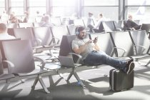 Man with headphones waiting at airport departure lounge — Stock Photo