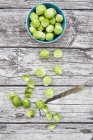 Top view of green Brussels sprouts in bowl and on wood — Stock Photo