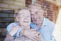 Elderly couple embracing at home looking through window — Stock Photo