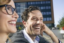 Portrait of laughing businessman and businesswoman sitting in front of office building — Stock Photo