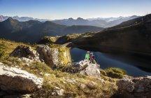 Jovem casal de Austria, Altenmarkt-Zauchensee, com bicicletas de montanha, sentado na pedra nas montanhas — Fotografia de Stock