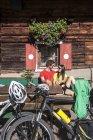Jovem casal de Austria, Altenmarkt-Zauchensee, sentado com bicicletas de montanha na cabana alpina — Fotografia de Stock