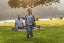 Щасливі хлопчик працює на луг з родиною на тлі — стокове фото