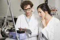 Cientistas que trabalham com tablet em laboratório analítico — Fotografia de Stock