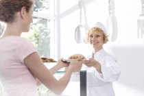 Confectioner handing over plate to waitress — Stock Photo