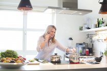 Жінка на мобільний телефон, приготування їжі на кухні — стокове фото