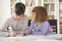 Two smiling sisters drawing at desk — Stock Photo