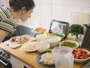 Frau auf der Suche nach Pealla Rezept im Internet mit Zutaten in Küche — Stockfoto