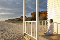 Португалия, Алгарве, женщина, занимающаяся йогой в доме на пляже на закате — стоковое фото