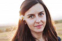Ritratto di donna sorridente con fiore dietro l'orecchio — Foto stock