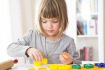 Bambina taglio fuori giallo modellazione argilla — Foto stock