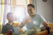 Vater und Sohn mit Saft Gläser zusammen frühstücken — Stockfoto