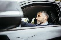 Portrait of man driving car, looking aside — Stock Photo