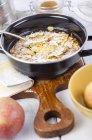 Esmalte cozinhar panela de suflê de maçã com amêndoas e açúcar de confeiteiro — Fotografia de Stock