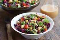 Азиатские шинкованной капусты салат с красной капустой, капуста, фасоль, кешью и кинза в глиняной миски и пластины на деревянных фоне — стоковое фото