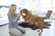 Woman playing with dog — Stock Photo