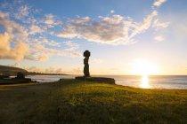Остров Пасхи, Ханга-Роа, Закат с каменной статуэткой Моаи в комплексе Тахай Церемониал на закате, археологическое место — стоковое фото