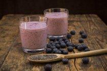 Due bicchieri di mirtillo radicchio frullato e cucchiaio di legno con semi di chia — Foto stock