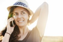 Donna sorridente che indossa cappello estivo telefonare con smartphone — Foto stock