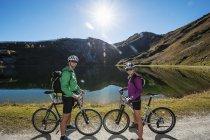 Австрия, Мбаппе, молодая пара с горными велосипедами на горном озере — стоковое фото