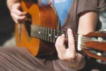 Nahaufnahme einer Frau, die Gitarre spielt — Stockfoto
