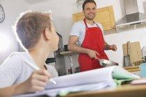 Vater, die Zubereitung von Speisen während seines Sohnes seine Hausaufgaben — Stockfoto