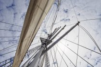 Rigging with sail of a sailing ship and cloudy sky — Stock Photo
