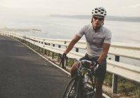 Велосипедист стоячи з велосипеді по дорозі на узбережжі і дивлячись на камеру — стокове фото