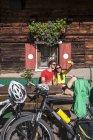 Jovem casal de Austria, Altenmarkt-Zauchensee, tirar uma foto com as bicicletas de montanha na cabana alpina — Fotografia de Stock