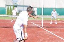 Jugadores seniors de tenis en cancha de tenis - foto de stock