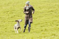 Woman running with dog on meadow — Stock Photo