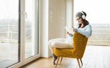 Sonriente mujer joven sentado en silla con tableta digital y auriculares - foto de stock