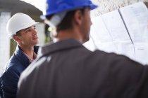 Будівельні робітники обговорювали плани будівництва — стокове фото