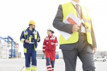 Three people wearing protective clothing walking at container port — Stock Photo