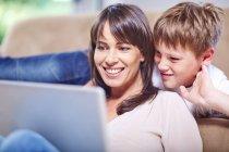 Sonriente madre e hijo usando portátil en casa - foto de stock