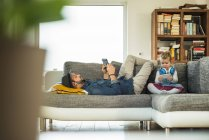 Father and daughter with digital tablet and smartphone on sofa — Stock Photo